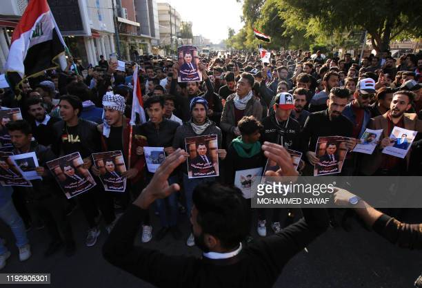 Iraqi demonstrators hold up photos of a fellow protester killed during the past three months of anti-government protests as thousands took to the...