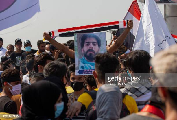 Iraqi demonstrators lift flags as they gather near the local administration building in the southern city of Basra on October 25 to mark the first...