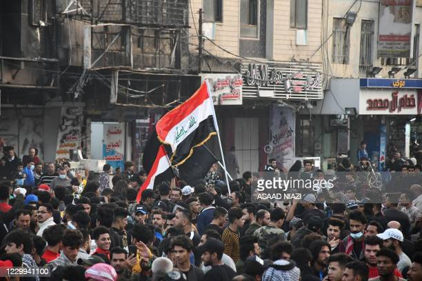 Iraqi demonstrators lift national flags as they gather in Habboubi Square in the southern city of Nasiriyah in Dhi Qar province, on December 4 to...