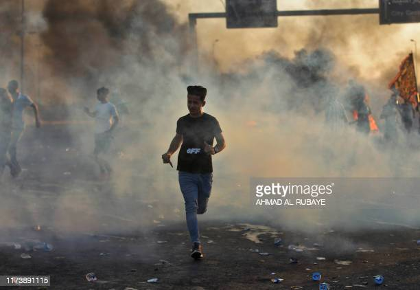 TOPSHOT Iraqi demonstrators run amidst smoke from burning tyres during a demonstration against state corruption failing public services and...