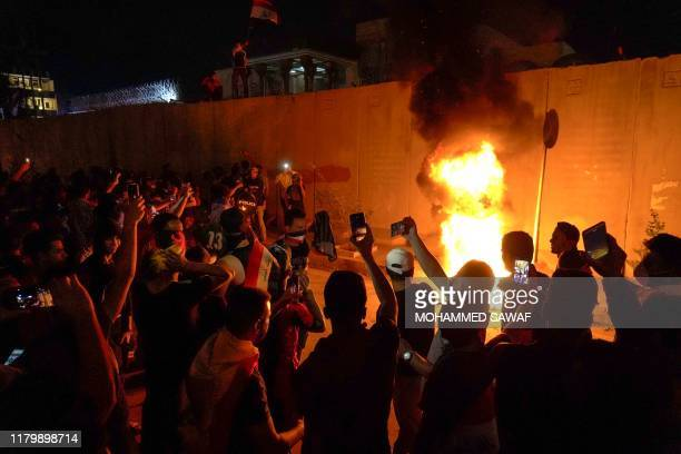Iraqi demonstrators set tires ablaze behind the walls protecting the Iranian consulate in the Shiite Muslim shrine city of Karbala, south of Iraq's...