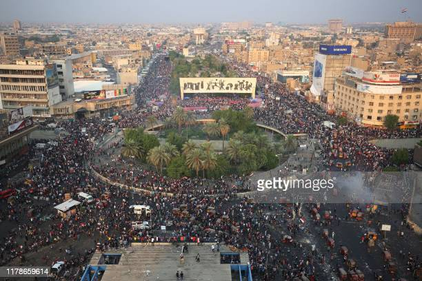 Iraqi demonstrators stand at Tahrir Square in Baghdad during ongoing anti-government demonstrations on October 28, 2019. - The Iraqi army announced...