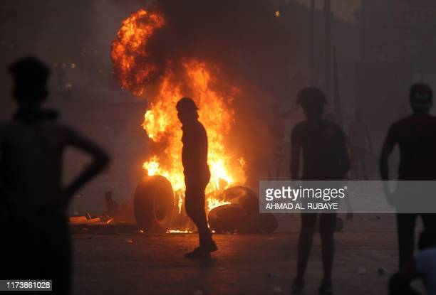 Iraqi demonstrators stand behind a tyre fire during a demonstration against state corruption failing public services and unemployment in the Iraqi...
