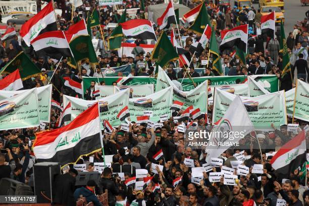 Iraqi demonstrators wave national flags and carry banners as they take part in an anti-government demonstration in the capital Baghdad's Tahrir...