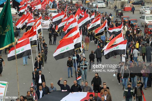 Iraqi demonstrators wave national flags as they take part in an antigovernment demonstration in the capital Baghdad's Tahrir Square on December 6...