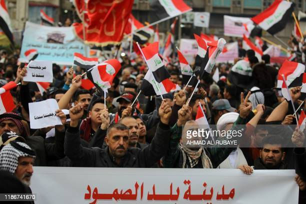 Iraqi demonstrators wave national flags as they take part in an anti-government demonstration in the capital Baghdad's Tahrir Square, on December 6,...