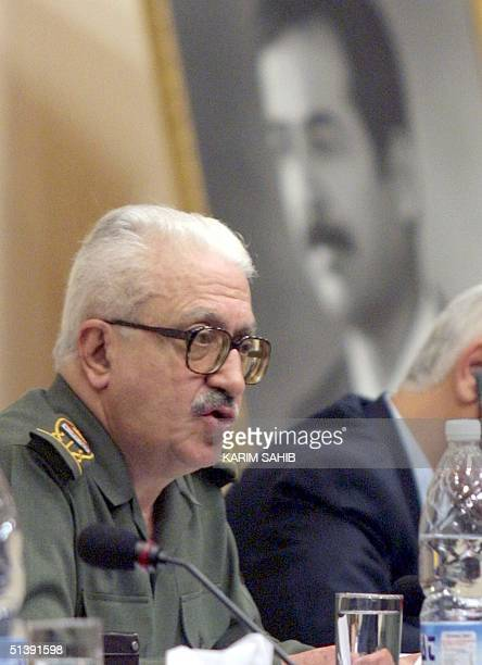 Iraqi Deputy Prime Minister Tareq Aziz, sitting in front of a giant portrait of Iraqi President Saddam Hussein, addresses the opening session of the...