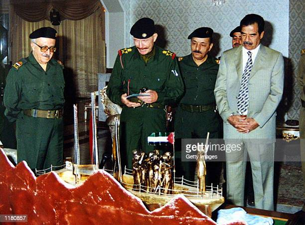 Iraqi Deputy Prime Minister Tariq Aziz Vice President Taha Yassein Ramadan Izat Ibrahim and President Saddam Hussein receive a gift from the Bath...