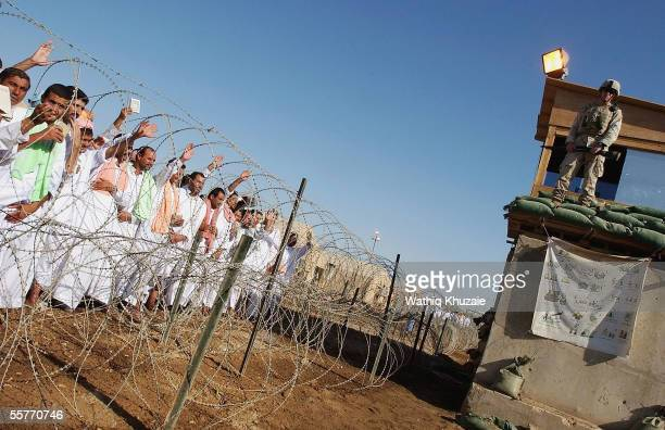 Iraqi Detainees wave as they stand in line to be processed for release from Abu Ghraib prison facility on September 26 2005 in Abu Ghraib 21 miles...