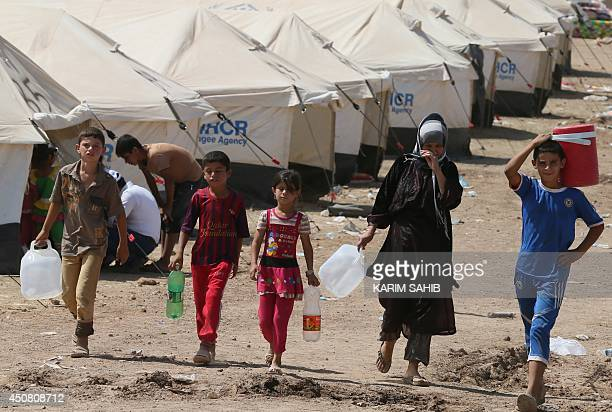 Iraqi displaced people carry jerrycans of water at a temporary camp set up to shelter Iraqis fleeing violence in northern Iraq on June 18 2014 in...