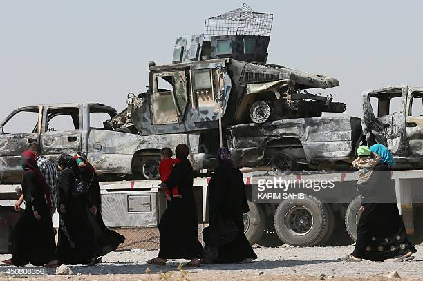 Iraqi displaced people who have fled violence in Iraq's northern Nineveh province walk past the wreckage of military vehicles upon their arrival in...