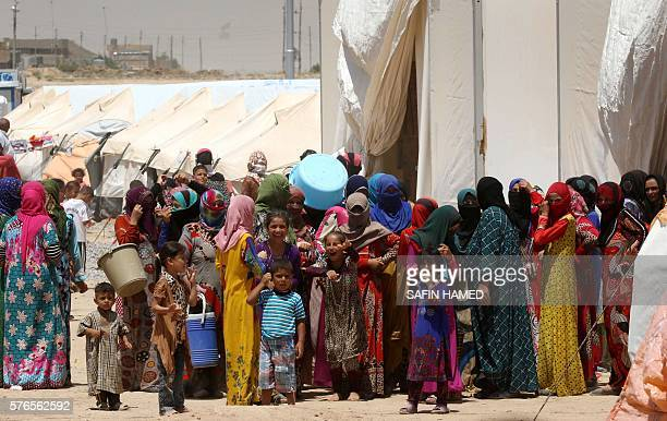 Iraqi displaced women and children who fled the violence in the northern city of Mosul gather outside a tent at the Dibaga camp on July 16 2016 in...