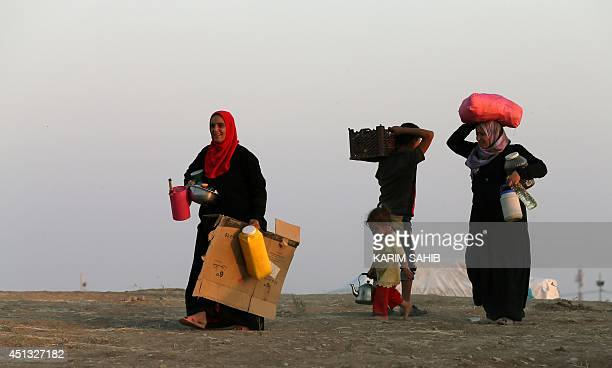 Iraqi displaced women carry jerrycans of water at a temporary camp set up to shelter people fleeing violence in northern Iraq on June 27 2014 in Aski...