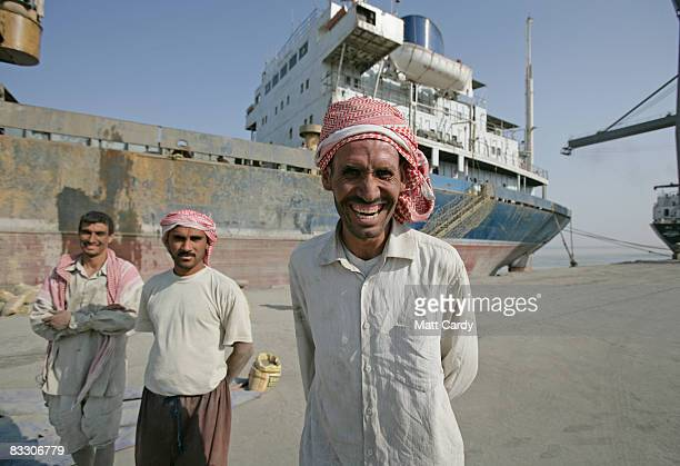 Iraqi dock worker laughs as British troops patrol the quay side at the port of Umm Qasr near Basra on October 16 2008 in Basra Iraq Business at the...