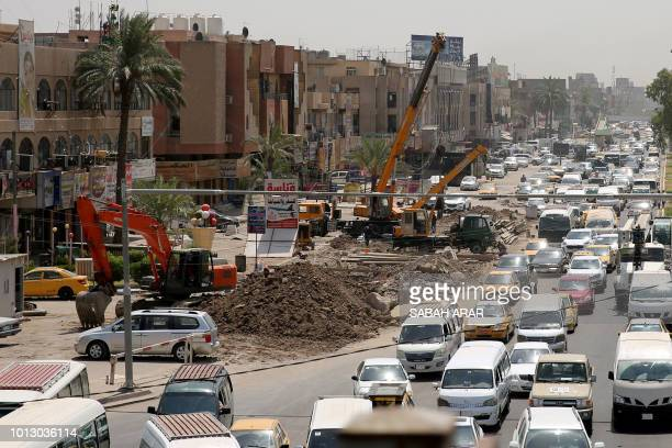 Iraqi drivers steer their cars in traffic jams next to street works in Baghdad on August 5 2018 More than 1000 streets and alleyways have been...
