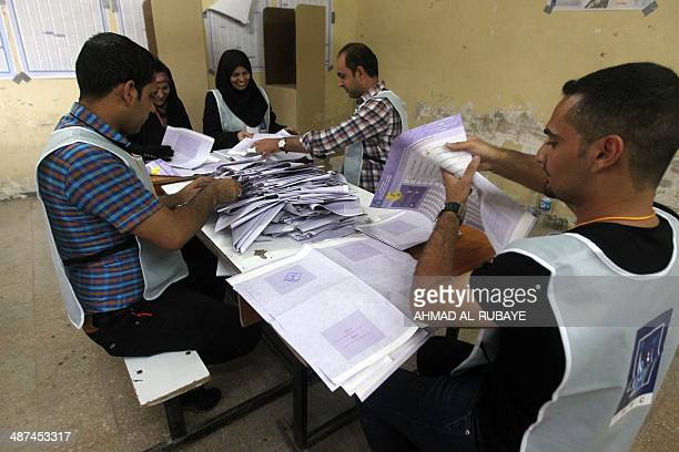 Iraqi election commission officials count votes at a polling station in Baghdad's Sadr City district on April 30 2014 Iraqis defied a rash of attacks...