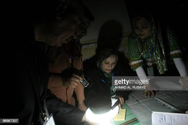 Iraqi election officials count votes using the light of a rechargeable battery lamp and a mobile phone due to an electricity outage at a polling...