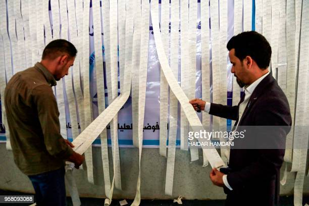 TOPSHOT Iraqi electoral commission employees examine electronic counting machine printouts in the central holy city of Najaf on May 13 for the...