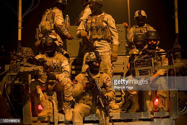 Iraqi Emergency Response Brigade members wait at a rallypoint as they prepare to serve an arrest warrant on a suspected insurgent responsible for...