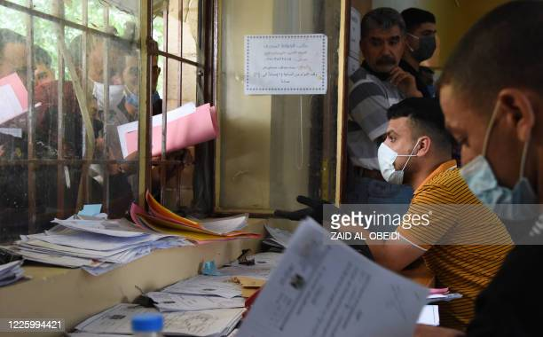 Iraqi employees at the general compensation department, in Mosul, wearing protective face masks against the Covid-19 coronavirus on June 15 speak to...