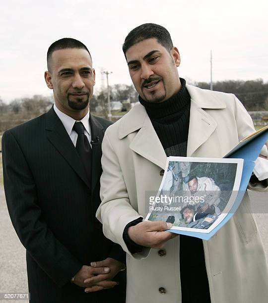 Iraqi expatriot Samir and Muhammed each of whom goes by their first name only show reporters a photo of Samir subduing Saddam Hussein as they prepare...