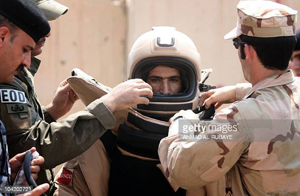 Iraqi explosives experts help a comrade gearup into a special suit for bomb disposal operations during a training session organised by their US...