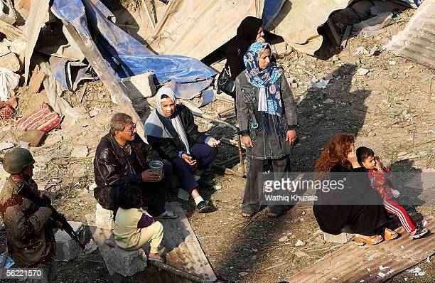 Iraqi families and residents of the collapsed building stand at the area where two suicide car bombs exploded near an Interior Ministry building...