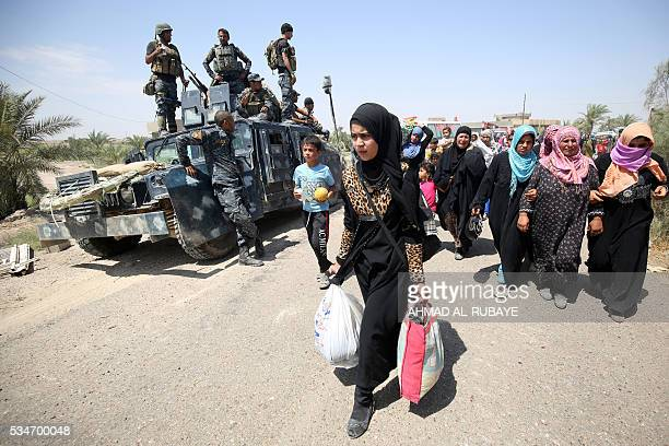 Iraqi families are pictured near al-Sejar village, in Iraq's Anbar province, after fleeing the city of Fallujah, on May 27 during a major operation...