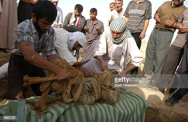 Iraqi families exhume the bodies of loved ones at a graveyard for nearly 1000 prisoners from Abu Ghraib prison whose remains are marked only by...