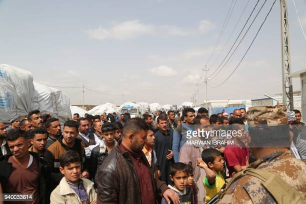 Iraqi families from the Hawija region who were displaced by fighting with Islamic State group fighters listen to the governor of Kirkuk as he speaks...