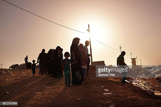 Iraqi families wait outside of a displacement camp for those caughtup in the fighting in and around the city of Mosul on June 26 2014 in Khazair Iraq...