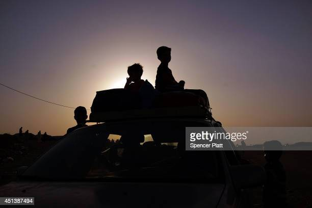 Iraqi families wait outside of a displacement camp for those caughtup in the fighting in and around the city of Mosul on June 28 2014 in Khazair Iraq...