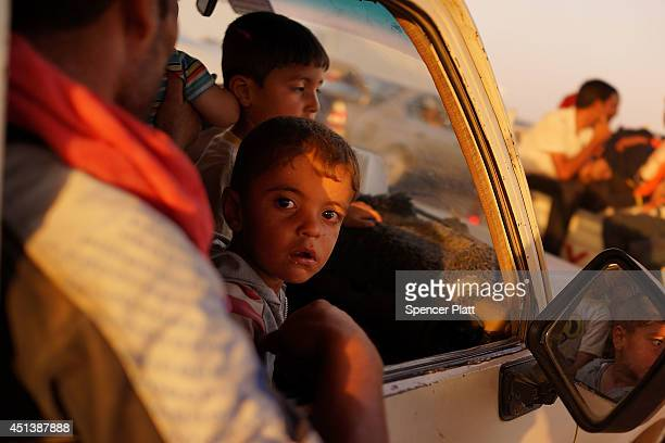 Iraqi families wait outside of a displacement camp for those caught-up in the fighting in and around the city of Mosul on June 28, 2014 in Khazair,...