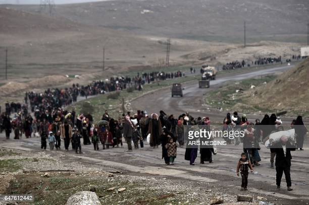 TOPSHOT Iraqi families walk down a road as they flee Mosul on March 3 during an offensive by security forces to retake the western parts of the city...