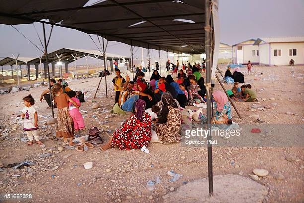 Iraqi families who fled recent fighting near the city of Mosul prepare to sleep on the ground as they try to enter a temporary displacement camp but...