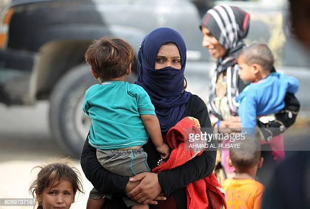 Iraqi families who fled the town of Hawija take refuge in the nearby town of Sharqat around 80 kilometres south of the city of Mosul on September 23...