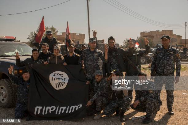 Iraqi Federal Police officers hold up a captured ISIS flag in the Islamic State occupied village of Abu Saif 6 kilometres from Mosul on February 22...