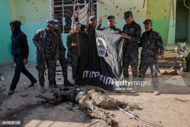 Iraqi Federal Police officers hold up a captured ISIS flag next to a dead Islamic fighter in the ISIS held village of Abu Saif 6 kilometres from...
