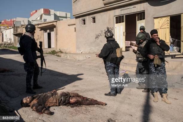 Iraqi Federal Police officers stand by a dead Islamic State fighter in the Islamic State occupied village of Abu Saif 6 kilometres from Mosul on...