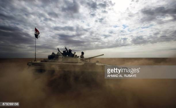 TOPSHOT Iraqi fighters flash the victory gesture from an advancing armoured personnel carrier as the Iraqi forces supported by members of the Hashed...