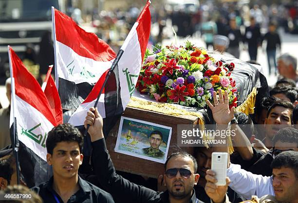 Iraqi fighters from the Popular Mobilisation units carry the coffin of their comrade Mostafa Hassan Shakir a student from the University of Kufa who...