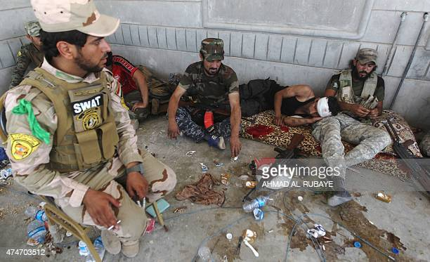Iraqi fighters from the Shiite popular mobilisation unit sit in the shade in the outskirts of Baiji refinery north of Tikrit in the Salahaddin...
