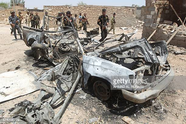 Iraqi fighters from the Shiite popular mobilisation unit walk past a damaged vehicle in the outskirts of Baiji refinery north of Tikrit in the...