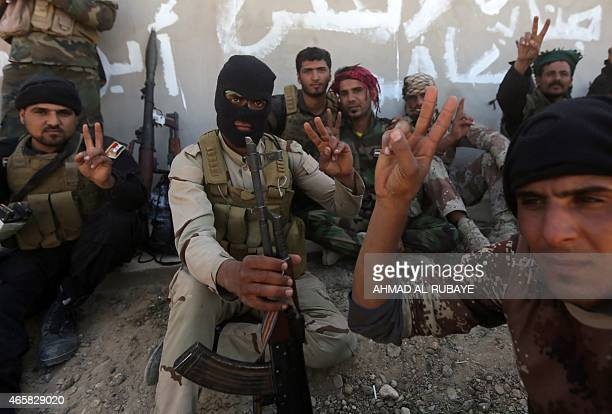 Iraqi fighters of the government-controlled Popular Mobilisation units flash the sign of victory as they take part in a military operation on the...