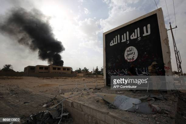 Iraqi fighters of the Hashed al-Shaabi stand next to a wall bearing the Islamic State group flag as they enter the city of al-Qaim, in Iraq's western...