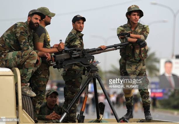 Iraqi fighters of the Hashed alShaabi units stand guard during a campaign gathering for the Fateh Alliance a coalition of Iraniansupported militia...