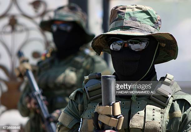 Iraqi fighters of the Shiite group Asaib Ahl alHaq stand guard outside their headquarters on May 18 2015 in the Iraqi mainly Shiite southern city of...