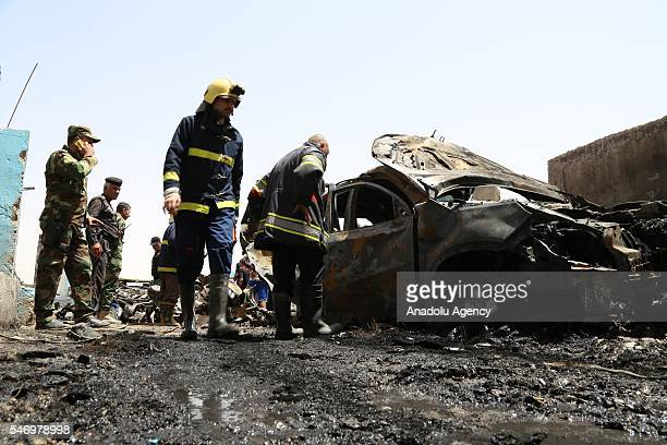 Iraqi fire brigade crew is seen beside the damaged car after a bomb attack over the military check point in Baghdad's Saab district in Iraq on July...