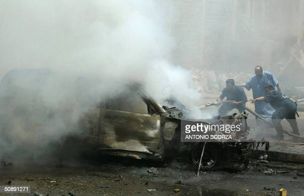 Iraqi firefighters extinguish fire from a burning Sport Utility Vehicle after it was attacked 500 meters far from the heavily guarded USled coalition...