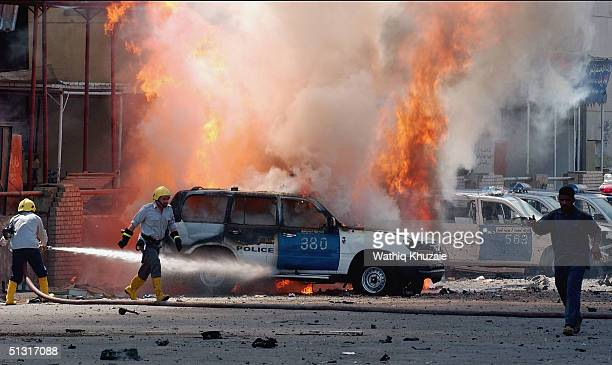 Iraqi firemen battle a burning police car September 17 2004 at the site of a suicide car bomb attack in central Baghdad Iraq A suicide car bomb...